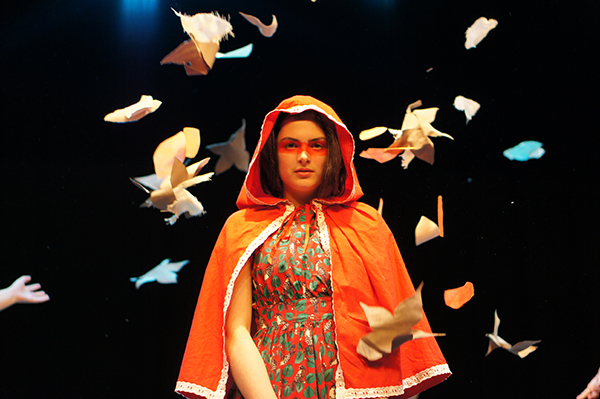 A young performer stands on a dark lit stage in a orange hooded cloak surrounded by paper origami birds floating around her.