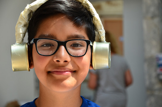 A young boy with black rimmed glasses smiles at the camera with a part of crafted gold foil headphones over his ears.